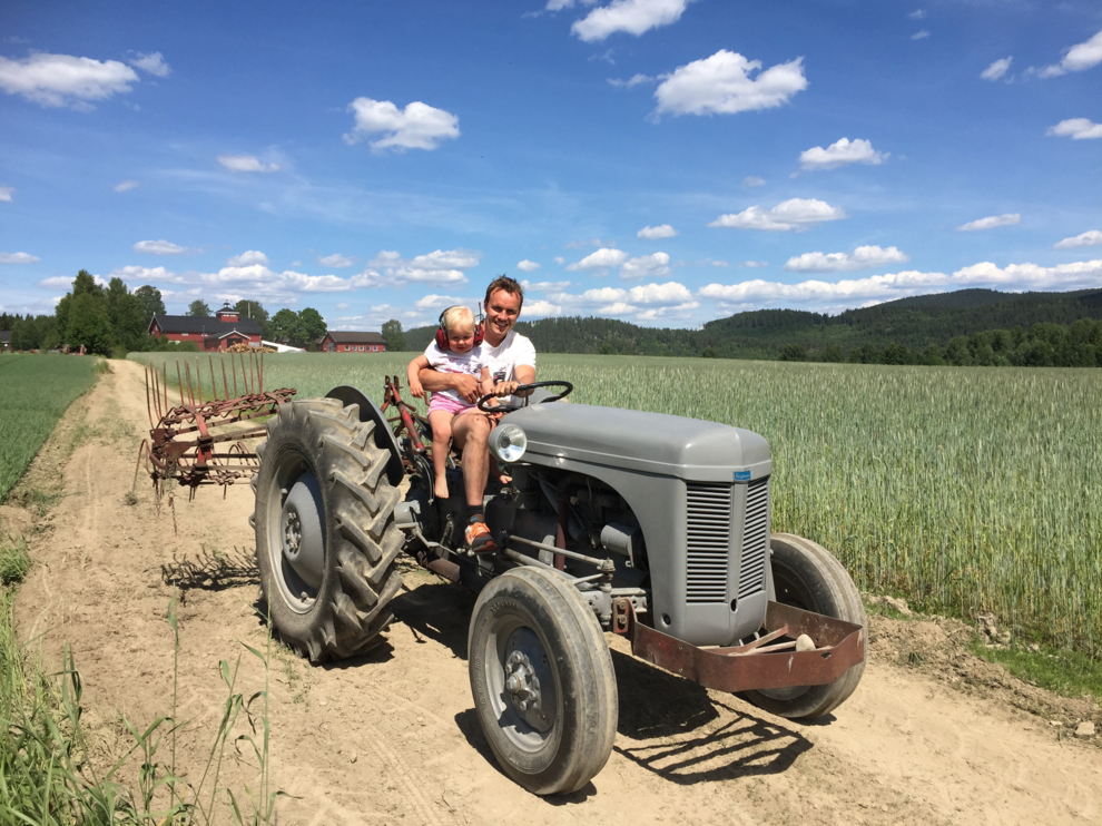 dad and girl drives old tractor